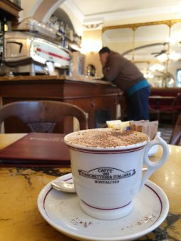 cup of coffee on table with interior of cafe in the background