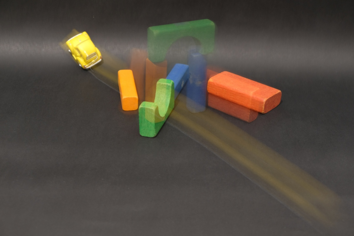 Motion-image of toy car toppling wood blocks