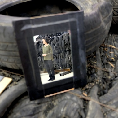 Woman standing reflected in mirror resting on old tires